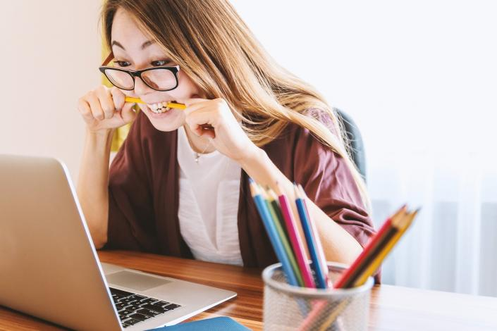 Woman looking at laptop with pencil in mouth learning
