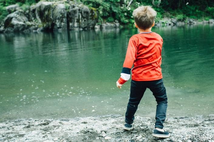 Child standing near a river