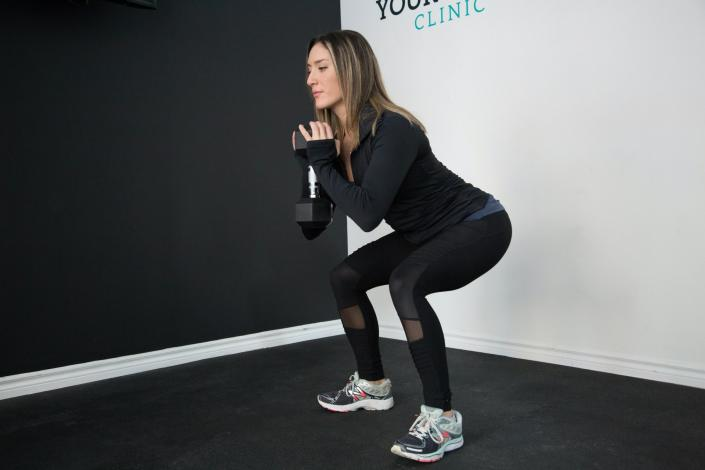 Woman squatting with dumbbell