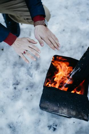 Getting warm by fire in snow