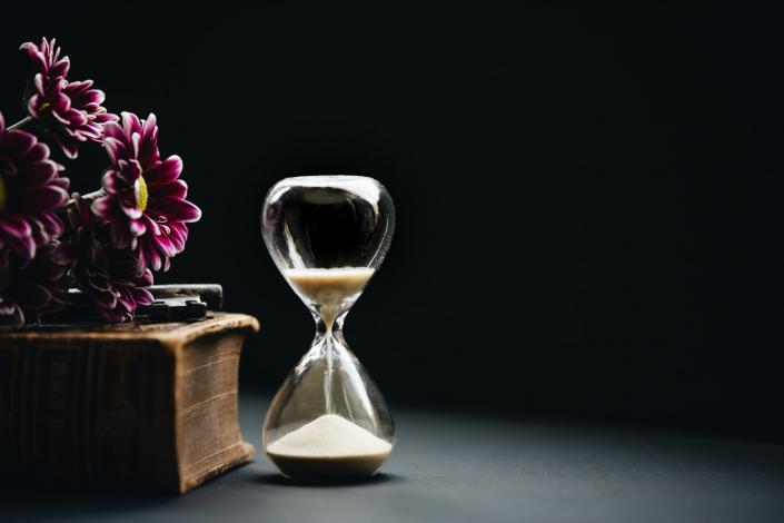 Hourglass sitting next to flowers