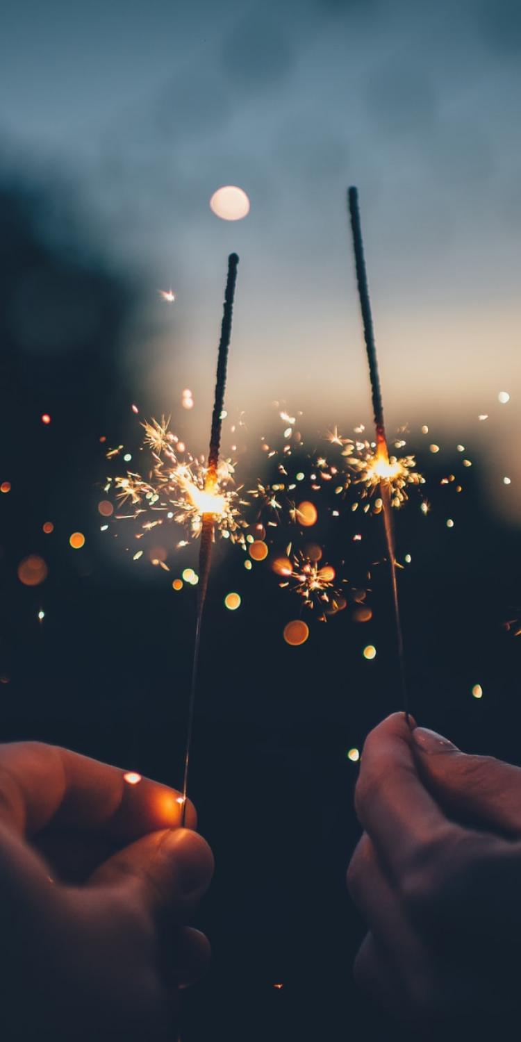 Two sparklers being held