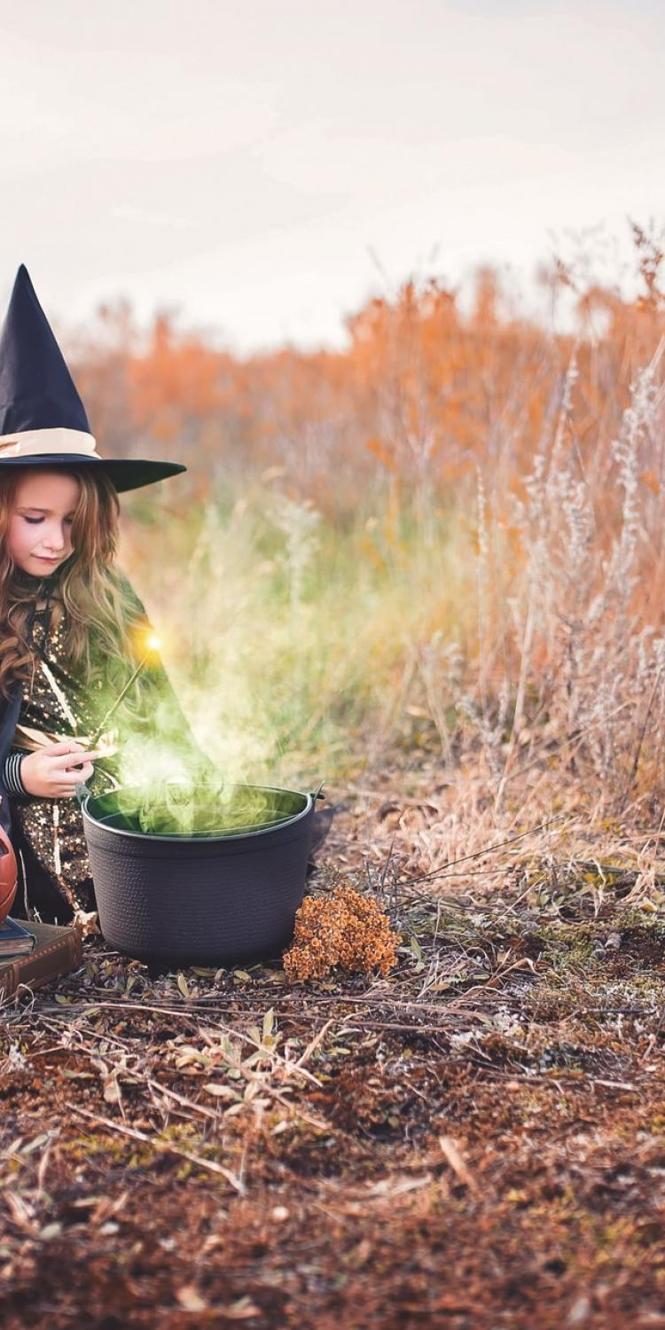 Girl in witch costume by cauldron